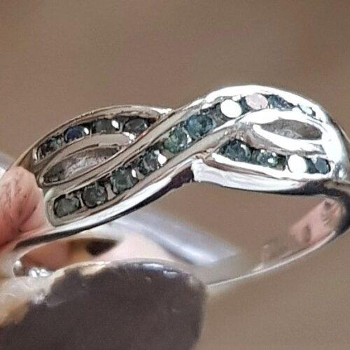 Varenummer : 170005 Virkelig Smuk og Yndig 10 Karat Hvidgulds Ring m. 18 Blå Diamanter, i alt 0,25 Carat. Hvidguld : 10 Karat Diamanter i alt : 18 Stk. Diamanternes Carat i alt : 0,25 carat Diamanternes Kvalitet : I1 - 2 Diamanternes Farve : Blå/Turkis Ringens bredde i front : 5 mm Ringens bund : 1,2 mm Ringens Vægt : 2,1 g. Ringens Str. : 54